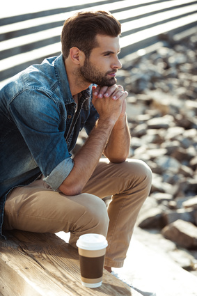 Relaxing outdoors. Top view of thoughtful young man keeping hands clasped and looking away while sitting outdoors