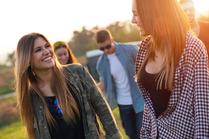 Outdoor portrait of group of friends having fun in field.