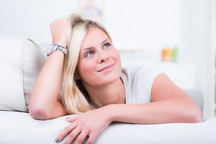 Hübsche blonde Frau träumt auf dem Sofa
