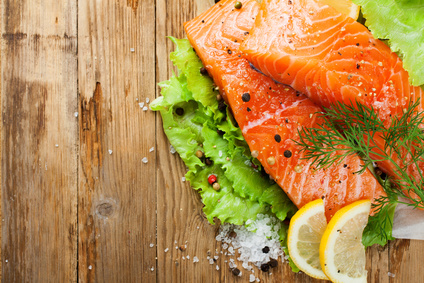 Delicious salmon fillet, rich in omega 3 oil, aromatic spices and lemon on fresh lettuce leaves on rustic wooden background. Healthy food concept. With copy space. Top view.
